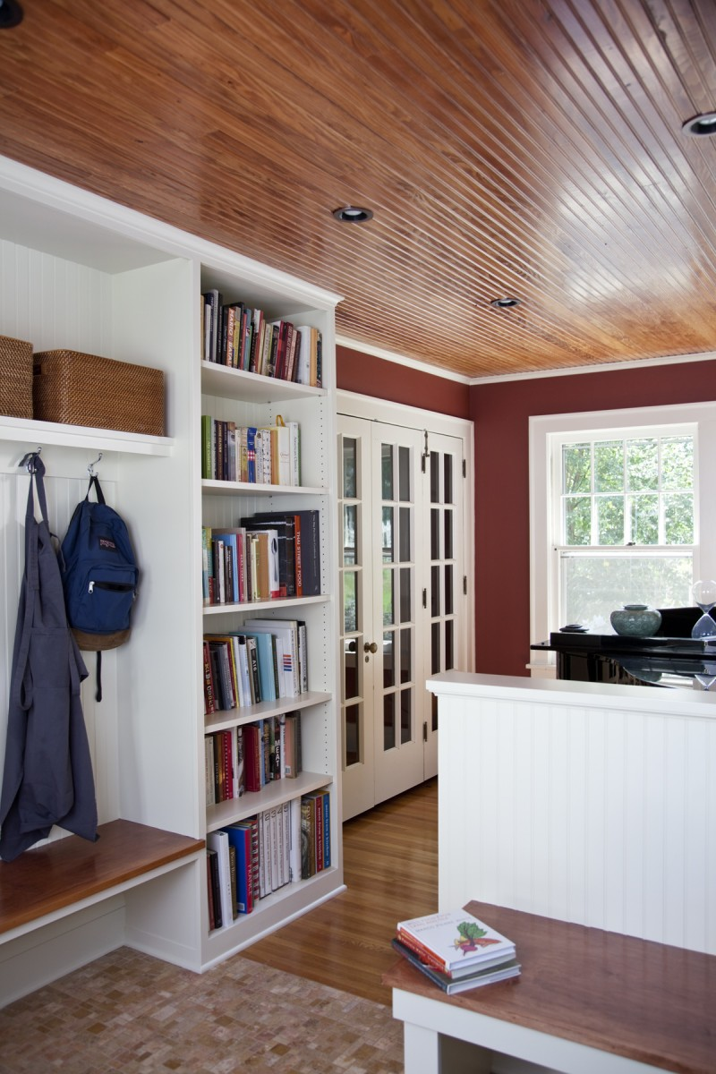 This mudroom was formerly a sunroom, but the active family needed a place to take off shoes and boots, and unload school and work supplies. TreHus carpenters built a custom bench, bookshelf and coat rack on site with beadboard accents to match the new ceiling. Relocating the back door from the kitchen to this room improved the flow of the home and gave this space increased function.