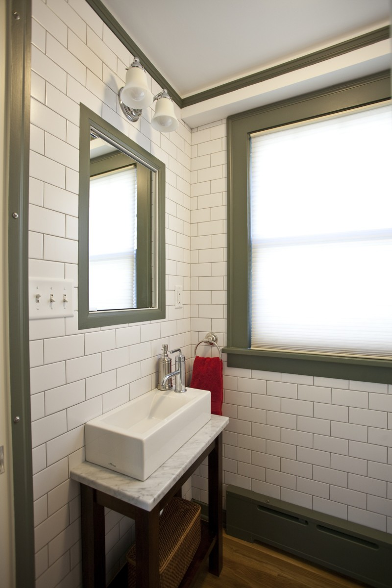 The powder room was remodeled with floor-to-ceiling subway tile, and features a custom-built vanity with a carrera marble top and a small, modern, console sink.