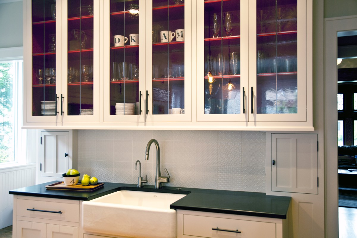 <p>The existinglaundry chute was cleverly integratedinto the new cabinetryanda shallow cabinet was repeated on the other side, in keeping with the overall theme of symmetry.A white tiled back splash featuresa textural mix of patterns, adding a modern touch to the design.</p>