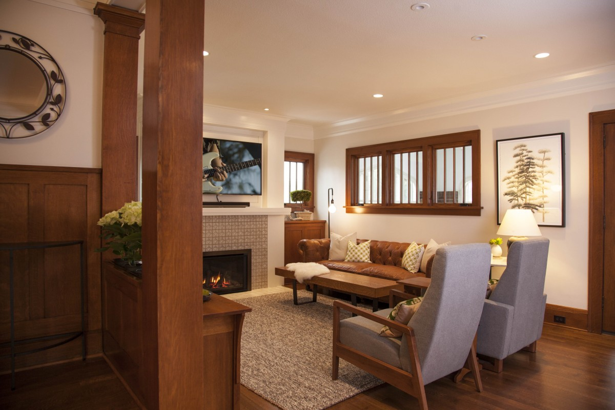 The interior of this Craftsman style home  was transformed to reflect more of the family's personal style. A mix of soft colors, textures, and bold patterns in the living room enhance the quartersawn oak trim and the client's collection of Arts and Crafts furniture. Large unused doors leading to the porch were replaced with high windows, allowing for a more functional seating arrangement.