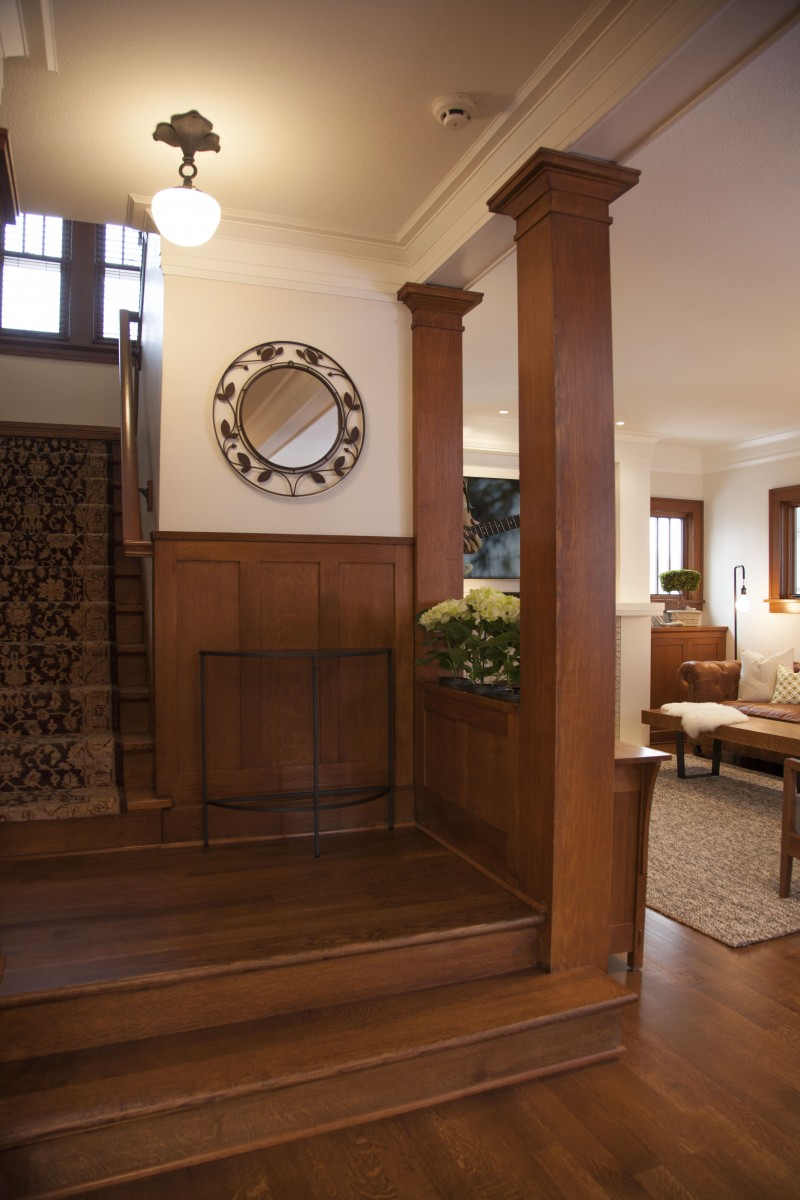 <p>The home's interior was transformed to reflect more of the family's personal style. A mix of soft colors, textures, and bold patterns in the living room enhance the quartersawn oak trim and the client's collection of Arts and Crafts furniture. Large unused doors leading to the porch were replaced with high windows, allowing for a more functional seating arrangement.</p>