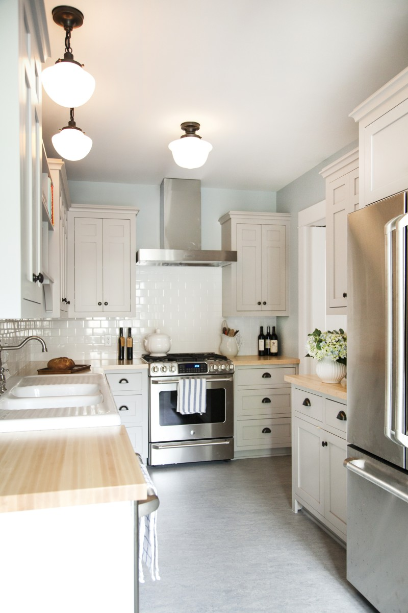<p>Traditional materials like school-house lights and authentic linoleum flooring as well as oil-rubbed bronze hardware, gives the kitchen a traditional feel without being dark or heavy.</p>