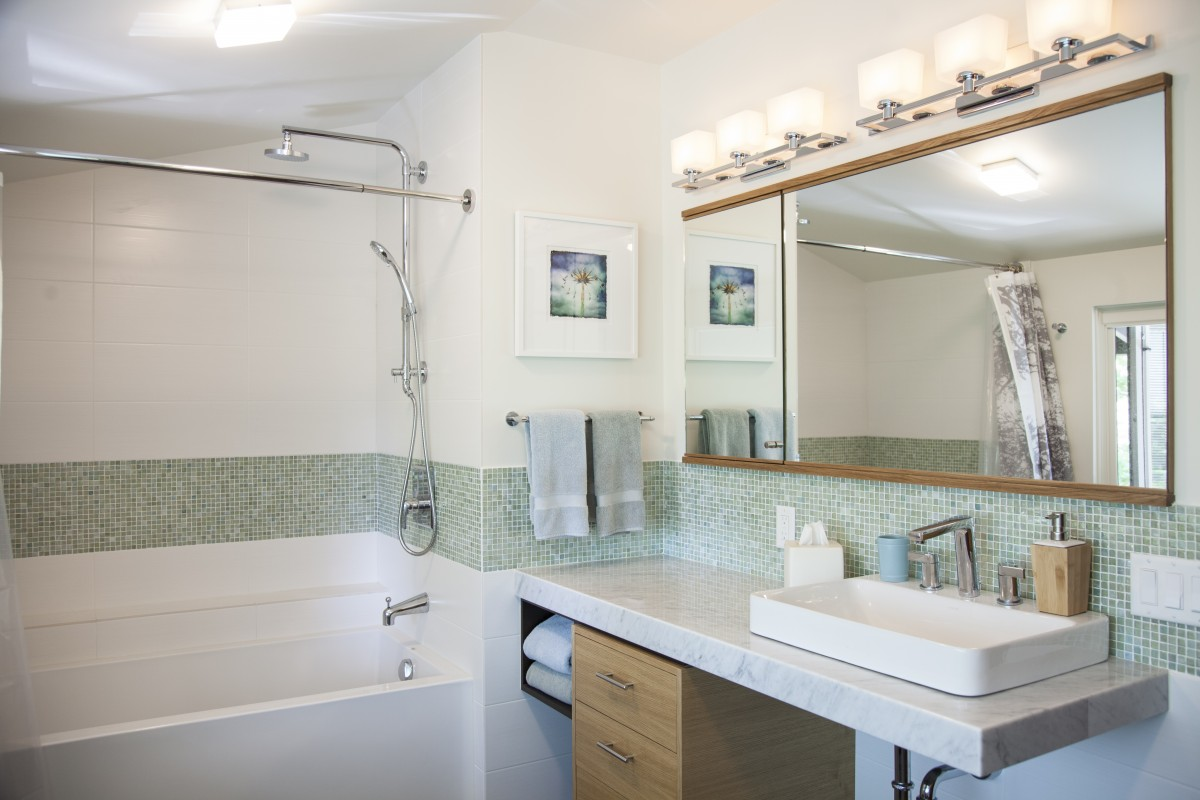 <p>The original gray and white finishes of this bathroom were enlivened by a colorful deco tile, and warm, rift cut oak.  The cantilevered marble counter creates an accessible vanity while staying true to the modern architectural form of the home.</p>