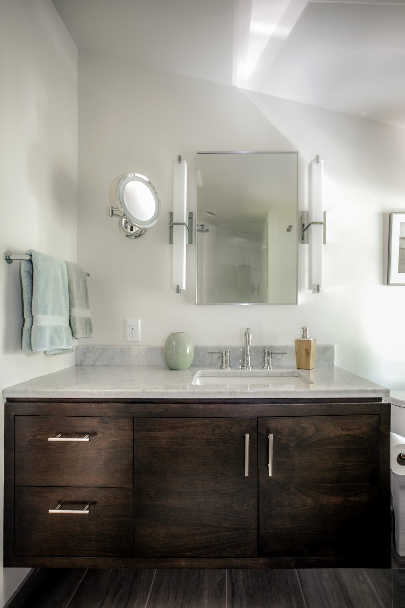 <p>The fixtures in this master bath were rearranged to create space for the shower that was lacking from the original.  A floating alder vanity with a marble top adds a touch of natural warmth.</p>