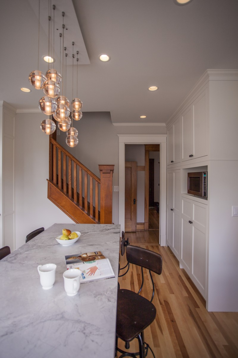 A sculptural light fixture over the island balances the more traditional stair baluster and pantry cabinets beyond.