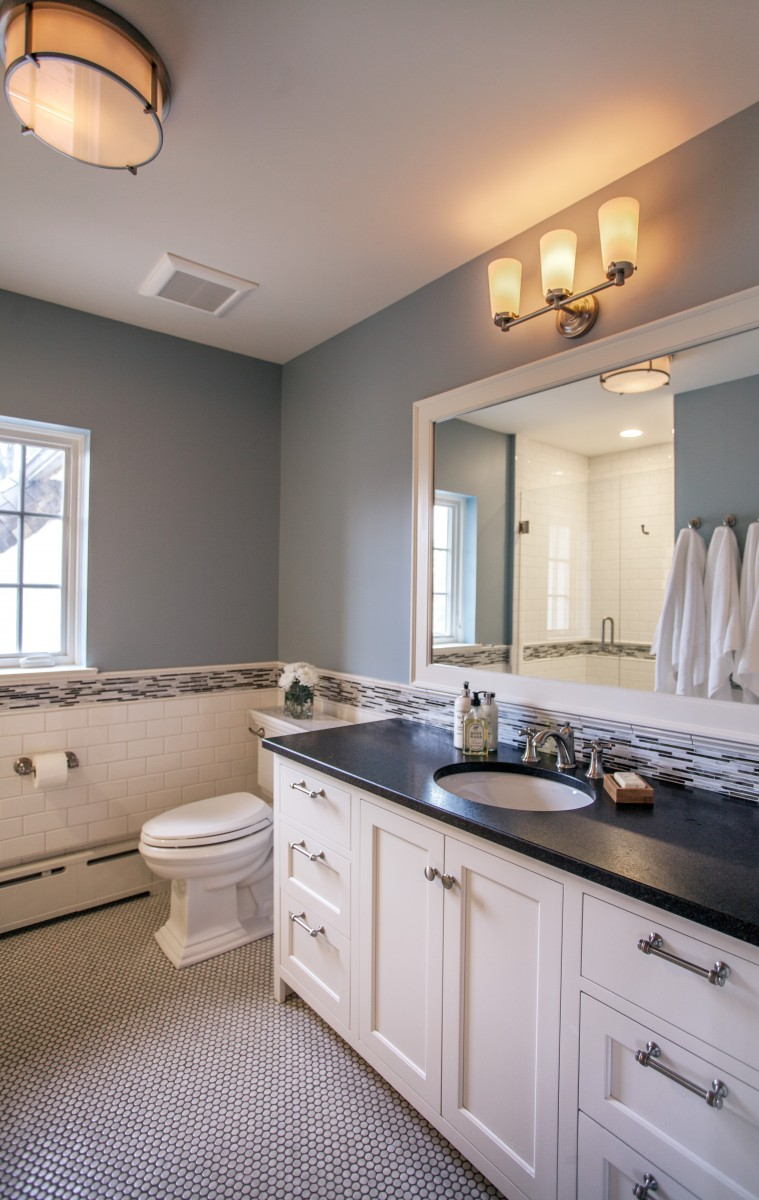 <p>A second floor bathroom was reconfigured with a new window, new fittings, cabinetry and lighting, and a penny-tile floor.</p>
