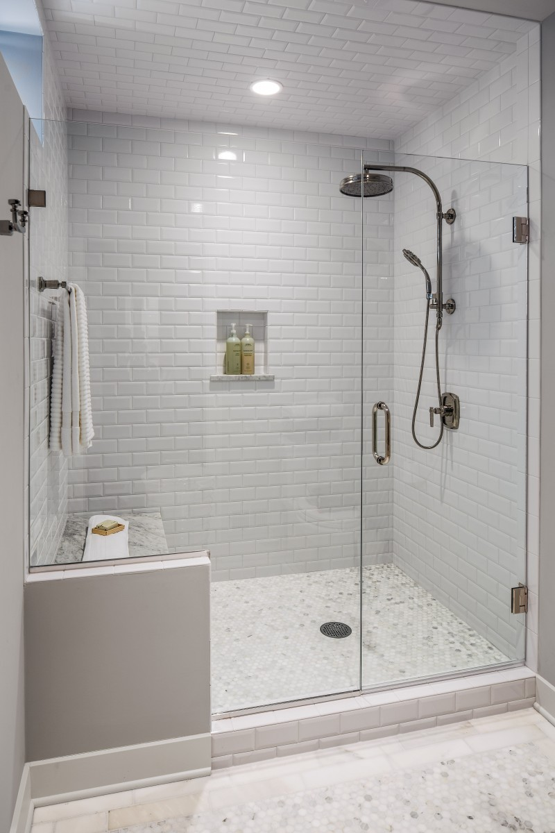 <p>The guest bath had a shower area that was dated and confining. A new frameless glass shower is roomier and allows in natural light. A built-in bench, marble floors and glazed subway tile walls and ceiling finish off this suite.</p>