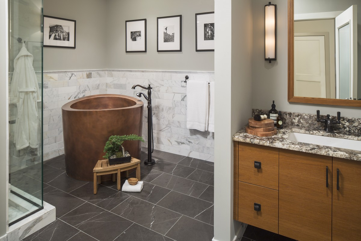 <p>Existing glass block and mosaic tiles were dated and in need of repair. A new copper Japanese-style soaking tub becomes the focal object in a suite that includes a shower, sauna, vanity area and a built-in bench. Warm natural materials including marble, travertine and teak help create a peaceful environment for this suite.</p>