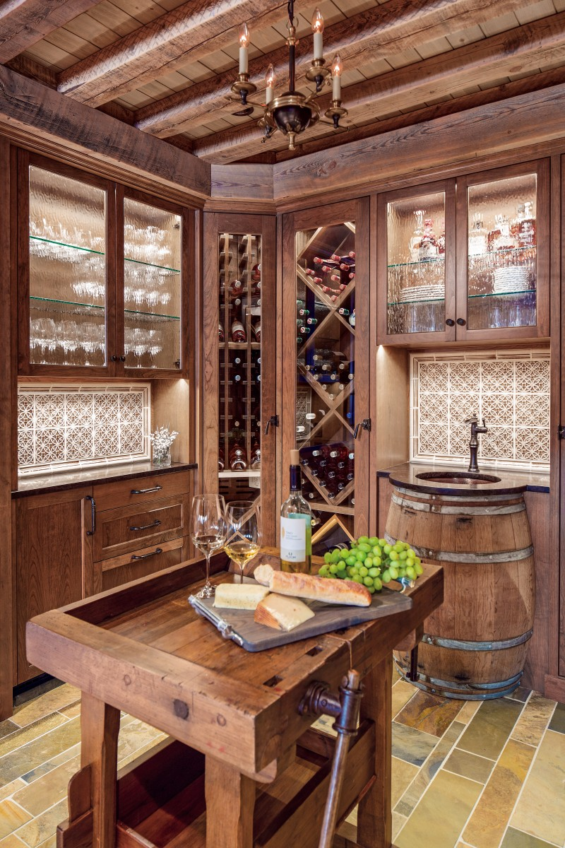 <p>This wine room consists of a slate floor, custom tile work, and a reclaimed timber ceiling. The built-in appliances help to create an inviting environment which includes a custom sink made from a wine barrel, and a serving table.</p>