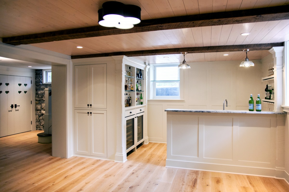 <p>The electrical and pipes had to be moved so the space could be used as a living area. The finished basement was built with a heated oak floor, pine tongue-and-groove paneling and reclaimed barn wood for the ceiling beams. Unique deep storage drawers take advantage of unused space under the staircase.</p>