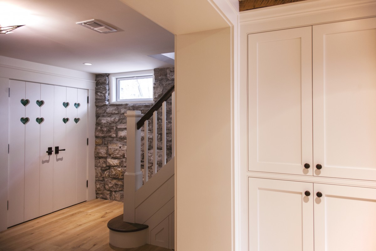 <p>Custom basement pantry doors were made with stained glass inserts and were repeated throughout the home. The original limestone foundation wall was left exposed, creating an accent wall.</p>