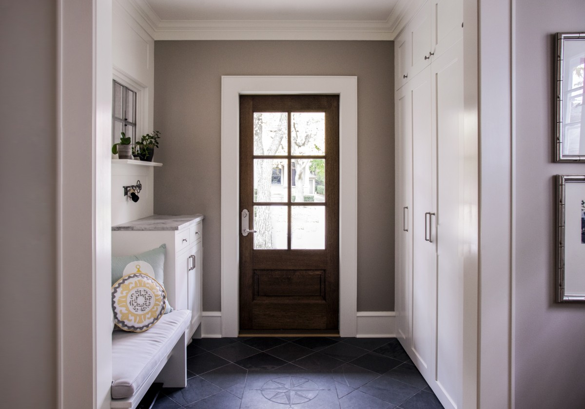 <p>The entryway was opened up to create a more welcoming and spacious foyer. A built in bench and floor-to-ceiling cabinets create storage.</p>