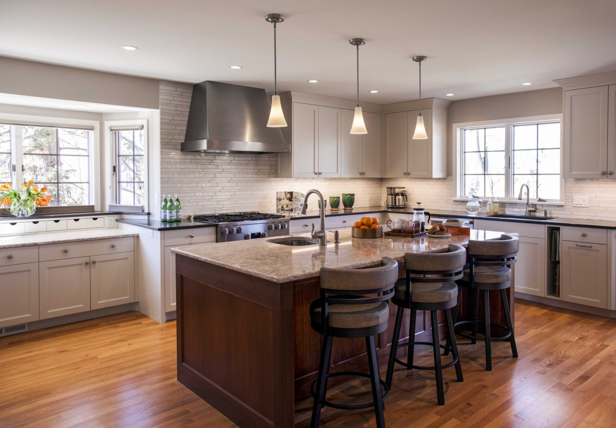<p>This beautiful kitchen was expanded and opened up to the dining room. An island, pendant lighting, new cabinets and mottled glass tile help to create a clean, spacious kitchen comfortable for both entertaining and cooking.</p>