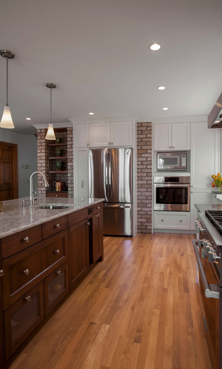 <p>The backside of the existing brick fireplace was reconditioned to house the refrigerator, pantry and display cabinets.</p>