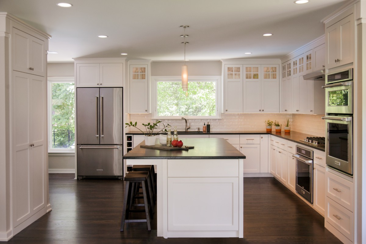 Thewhite tile backsplash, glass-paned upper cabinets and pendant lighting add sophistication to the kitchen.The design of this kitchen allows room for entertaining both family and friends.