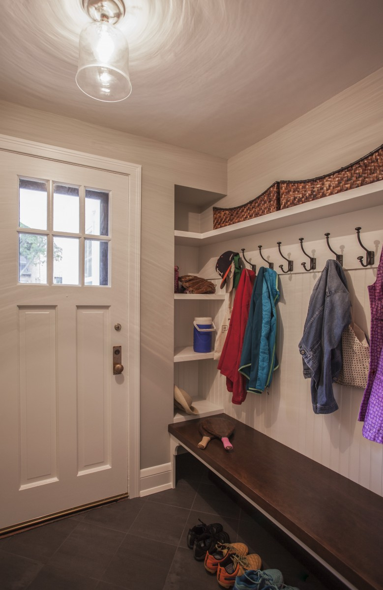 The back door was moved to be flush with the garage and in doing so created room for a mini mudroom. It is simple in design with shelves, hooks and a bench to create room and storage for this active family.