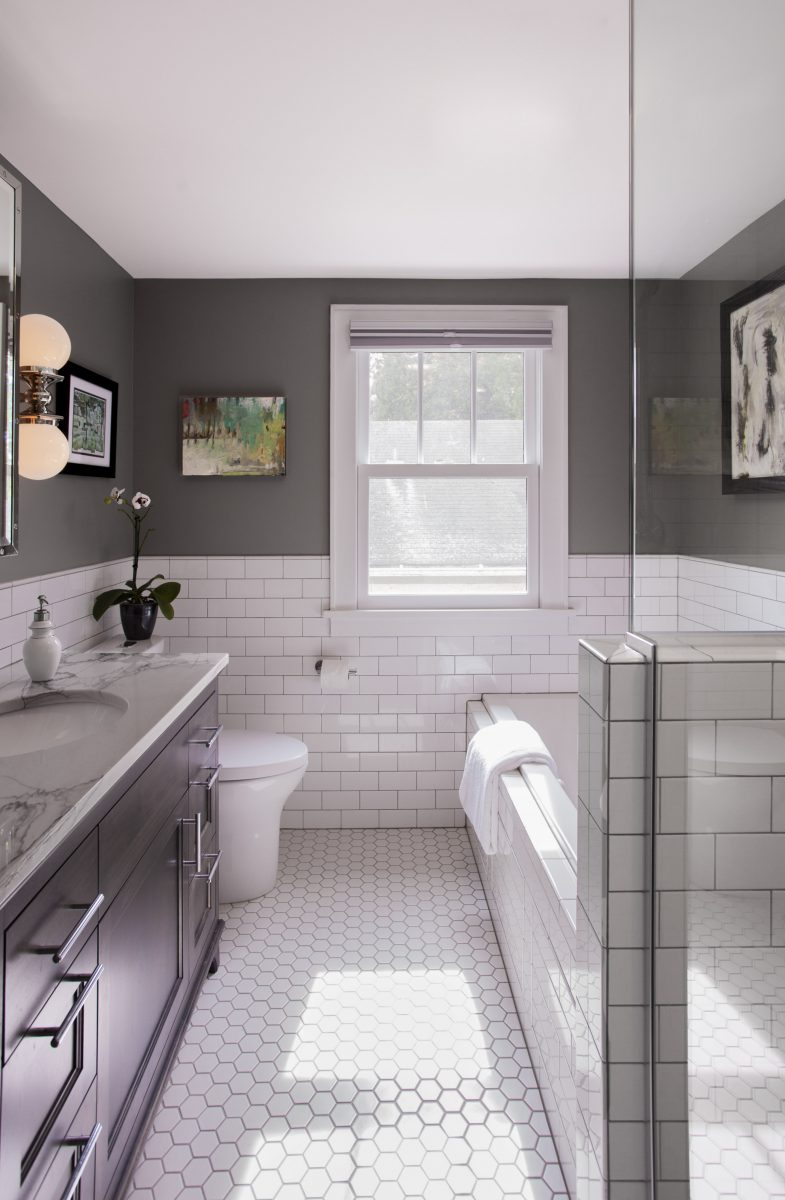 <p>Clean 3×6 Subway tiles were paired with dark grout for a crisp feel. The floor, though simple and unembellished, forms a strong contrast against the wall color and dark vanity.</p>