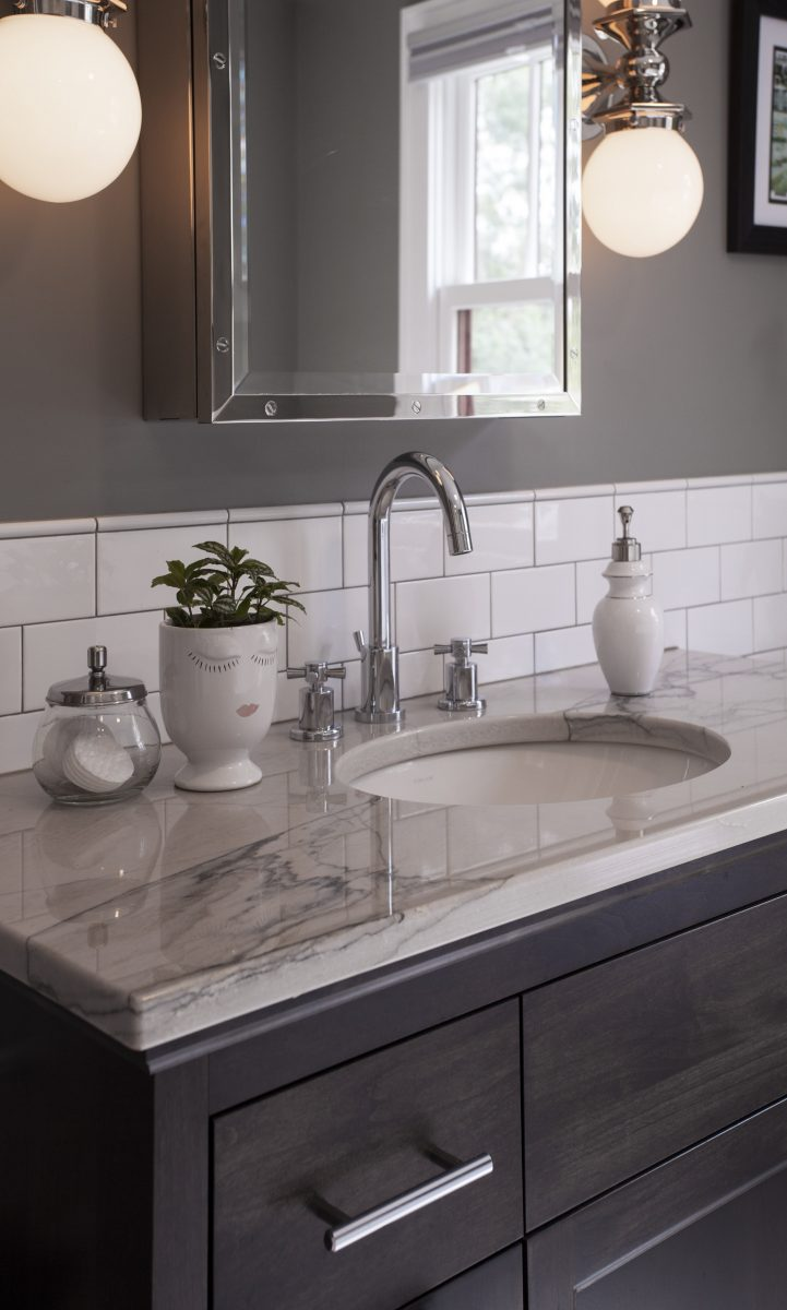 An undermount sink, a furniture-like vanity, granite countertops, andinteresting finishing materials werekeytohelping thistransitional bathroom project stand out.