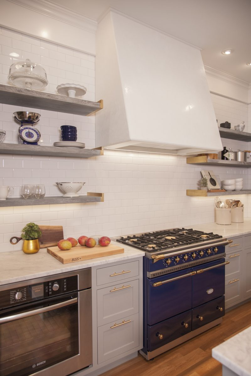 Open cerused oak shelving and white subway tiles give the kitchen an open feel, while a handmade venetian plaster hood and custom brass shelf ends add an old-world feel to the space and accentuate the superb Lacanche stove.