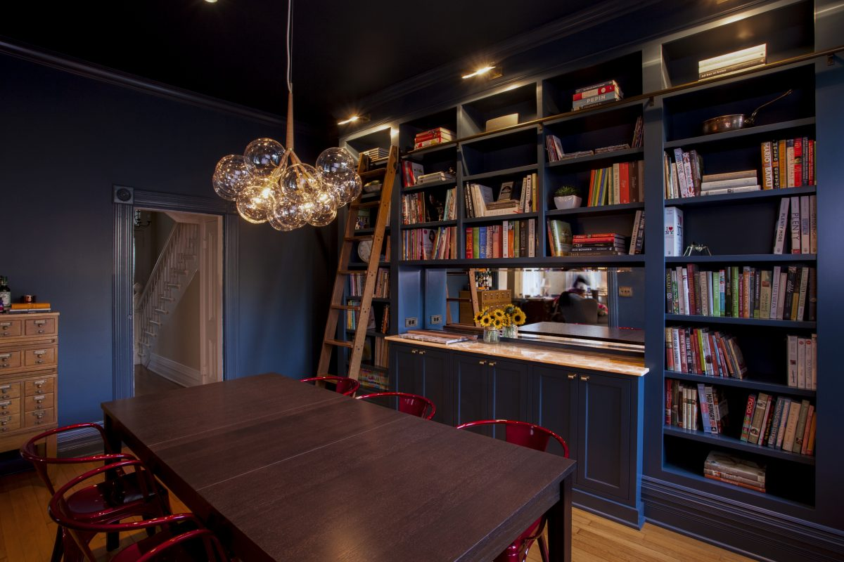<p>The dining room's deep blue color evokes the romance of a dusky sky, and the laddered bookshelf and handmade chandelier continue the kitchen's stylish ethos.</p>