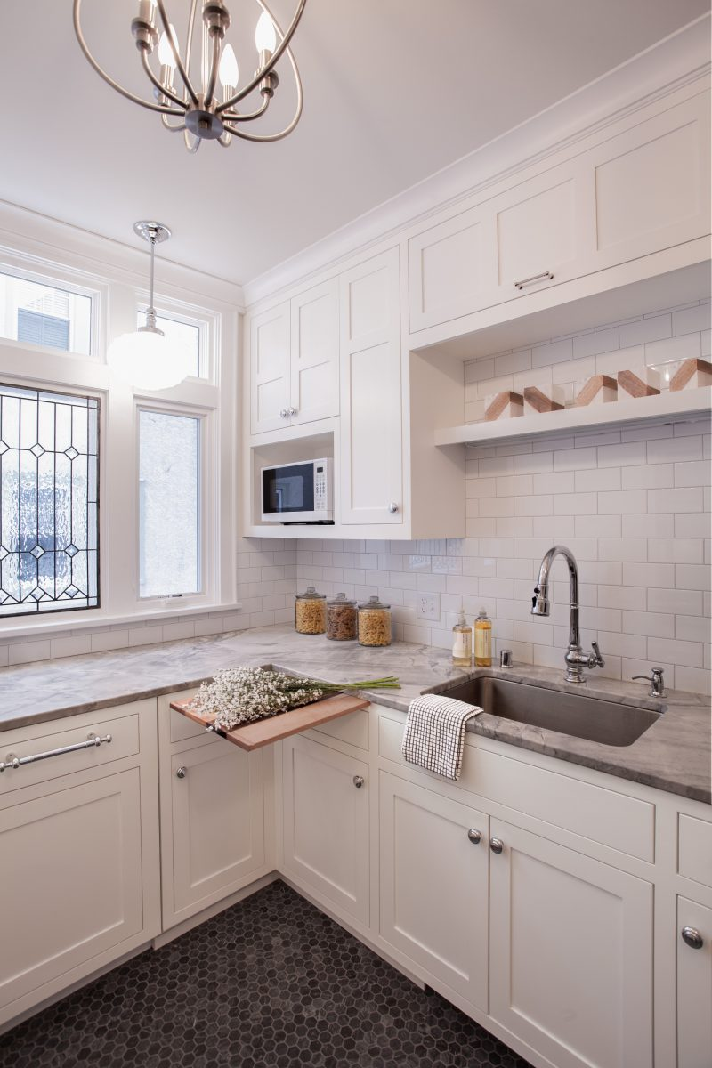 <p>Heartland appliances and a leaded glass tempered window lend a classic feel, while the hex marble flooring, white subway tile and pendant lighting create a clean, welcoming space.</p>
