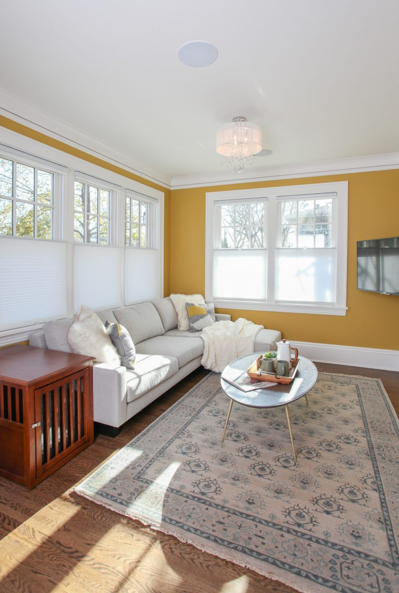 A traditional style living room was added off the kitchen in the new addition. A built-in bench, cubbies and coat hooks created an organized entry for the busy family. A large deck was added above the addition with great views of the backyard.