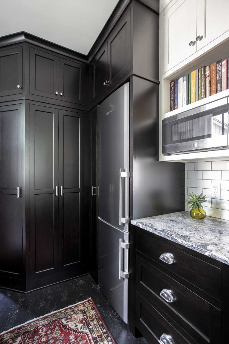 The extreme contrast of the almost black cabinetry and floor vs. the light and bright walls and shelves gives this kitchen a bright, clean, and crisp appeal. The floor is Marmoleum which is a nod to the linoleum that would have been used originally.