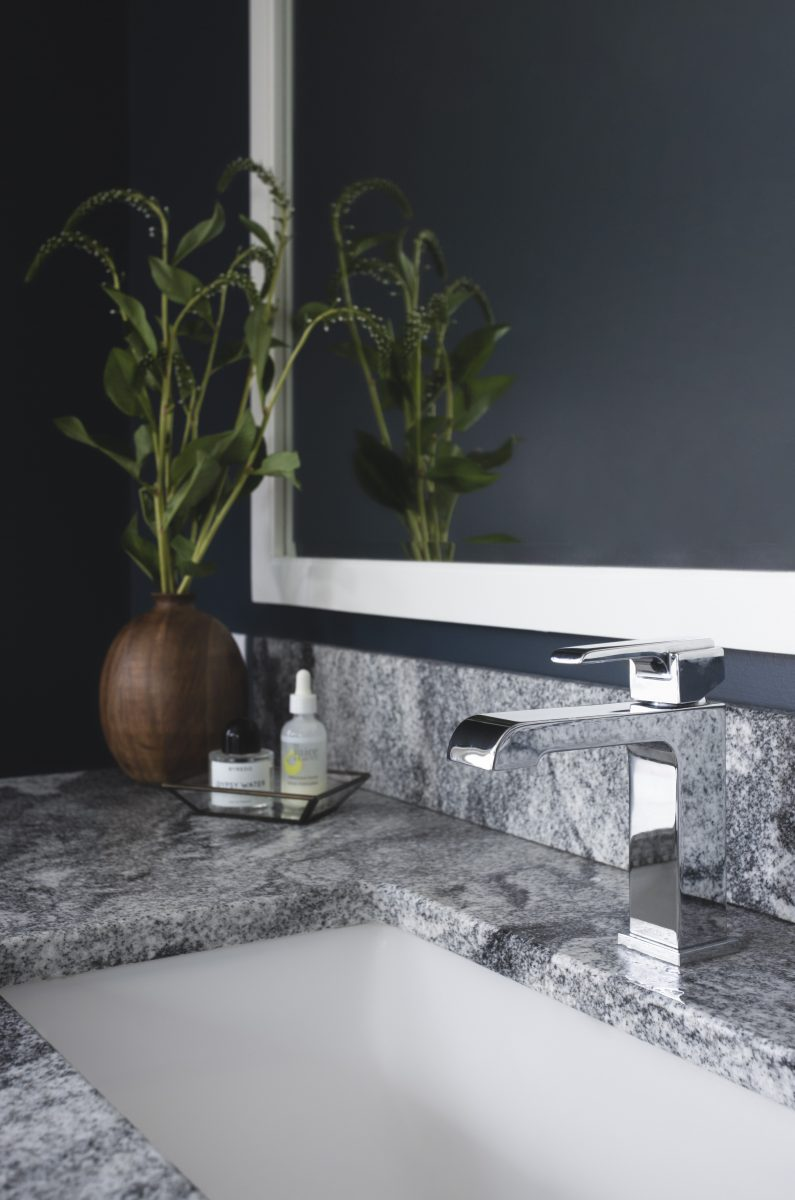 The Viscon white granite countertop adds a subtle texture to the purchased vanity and contrasts beautifully with the dark walls and black hexagon floor tile.
