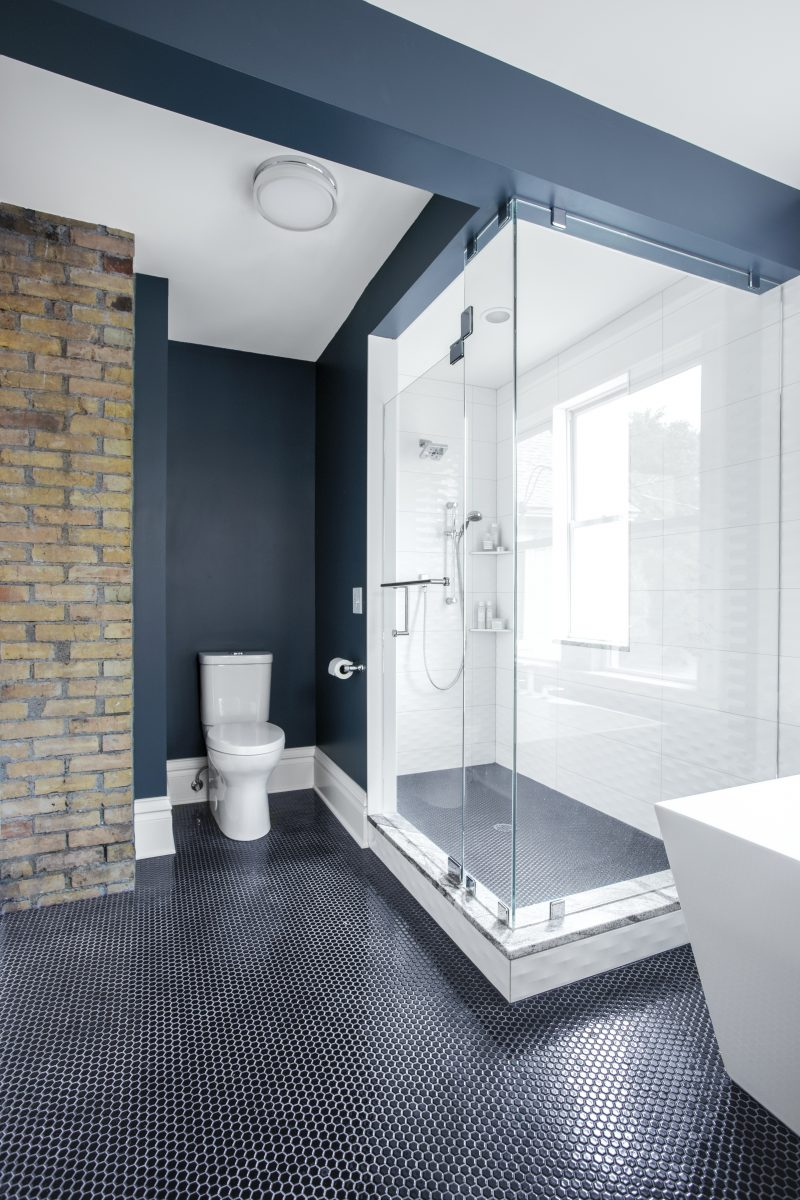 <p>The large walk-in shower doors have a floor-to-ceiling frameless design, creating the sense of space. Rich navy walls emphasize the white shower tiles and large soaking tub. The brick chimney flue was exposed to bring the character and warmth of the house into the new space.</p>