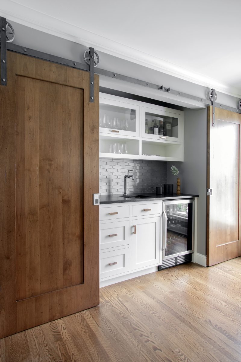 <p>The bar is framed with distressed barn doors that can slide open and closed to provide hidden spaces for access to the pantry, microwave, and freezer.</p> <p>&nbsp;</p>