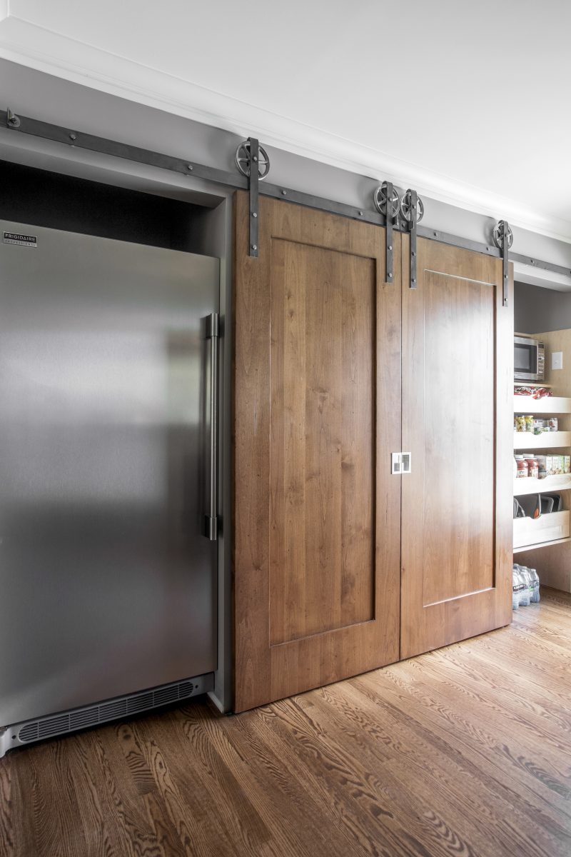 <p>The bar is framed with distressed barn doors that can slide open and closed to provide hidden spaces for access to the pantry, microwave, and freezer.</p> <p>&nbsp;</p> <p>&nbsp;</p>