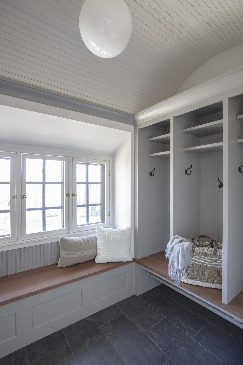The existing mudroom's windows and doors left little room for practical storage. New locker cabinets were created and the existing windows were modified and re-used in a new bay, creating space for a bench.