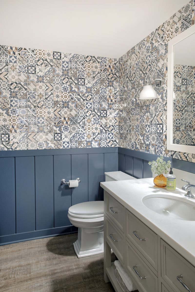 An awkward nook tucked behind the stairs was utilized to create a simple, playful bathroom. Inexpensive, patterned tile paired with a painted wainscot modeled off of the great room paneling brings a bit of whimsy to the walls and complements the custom vanity.