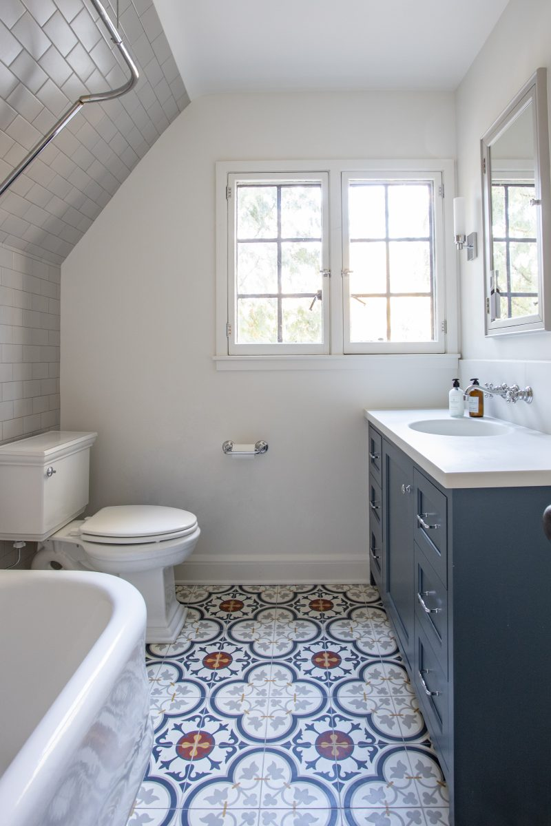 A vibrantly patterned floor tile brings a splash of color into the kids' bath and is paired with a Tender Grey subway tile on the shower wall. The original tub was left in place but refinished with a new custom shower rod installed to work around the existing sloped ceiling.